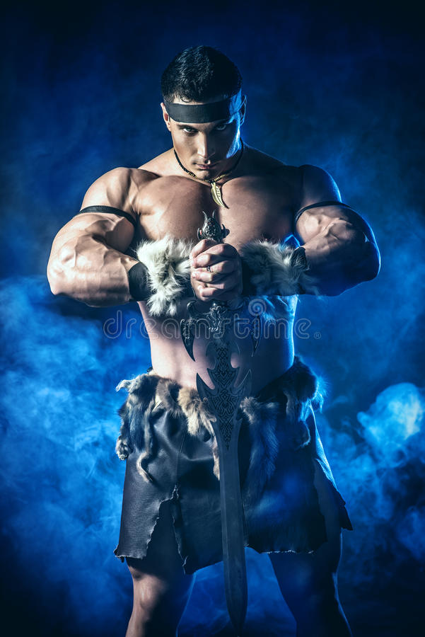 Historical hero. Portrait of a handsome muscular ancient warrior with a sword royalty free stock photography