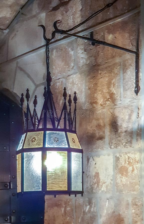 Historical interior: forged old pendant lamp with decor and multi-colored glass on a stone wall background stock photography