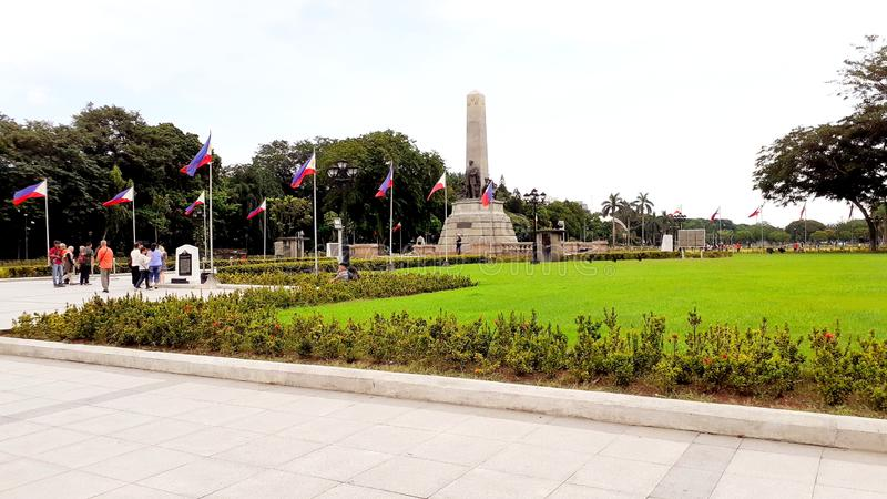 The historical Luneta Park also known as Rizal Park, only in the Philippines. Landscape, trees, people, statue, flags, place stock photography