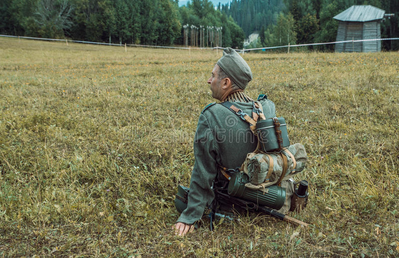Historical reconstruction second world war. A German soldier sitting on the grass. The soldier sitting on the grass and rubs weapons. Reenactment of second stock images
