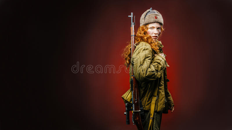Historical reenactment of soviet union army by pretty girl with. Mosin-nagan in beautiful light on red background royalty free stock photography