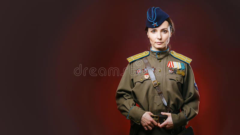 Historical reenactment of soviet union army by pretty woman. In beautiful light on red background royalty free stock image