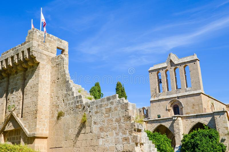 Historical ruins of the walls of medieval Bellapais Abbey in Turkish part of Cyprus. Captured with blue sky and green trees around. Significant tourist spot stock photography