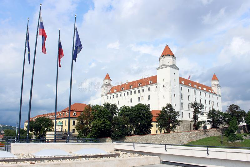 Historical white castle of Bratislava, dominating the capital of Slovakia. With national and europe flags stock photography