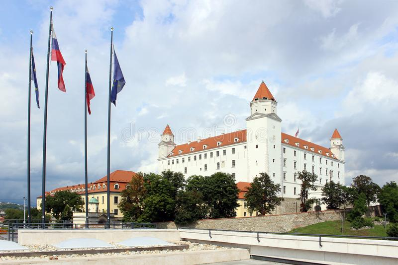 Historical white castle of Bratislava, dominating the capital of Slovakia. With national and europe flags stock image