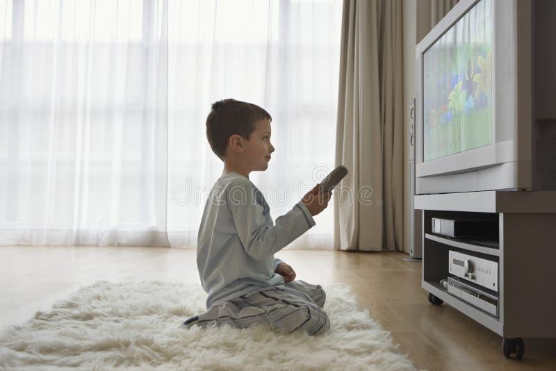 Historietas de observación del muchacho en la TV ilustración del vector