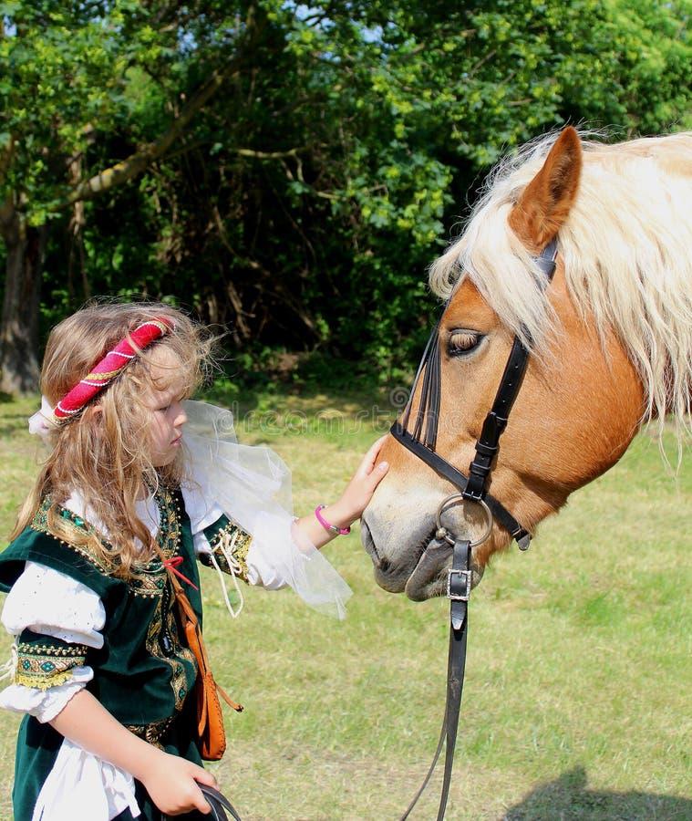 Historievänner - liten flicka i en historisk dräkt med en Hafflinger häst fotografering för bildbyråer