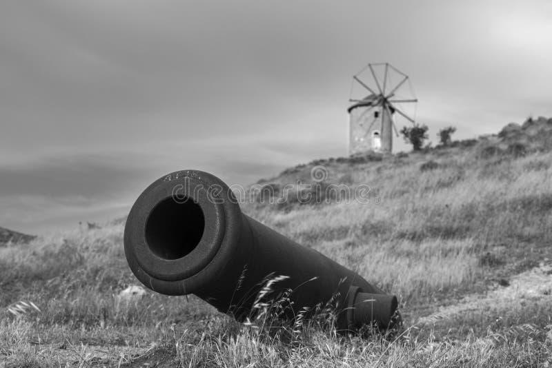 Historisch oud kanon met windmolenachtergrond in een weide B&W royalty-vrije stock foto's