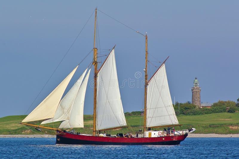 Historisch two-masted varend schip op zee met groene kust en grijze oude vuurtoren op de achtergrond stock afbeelding