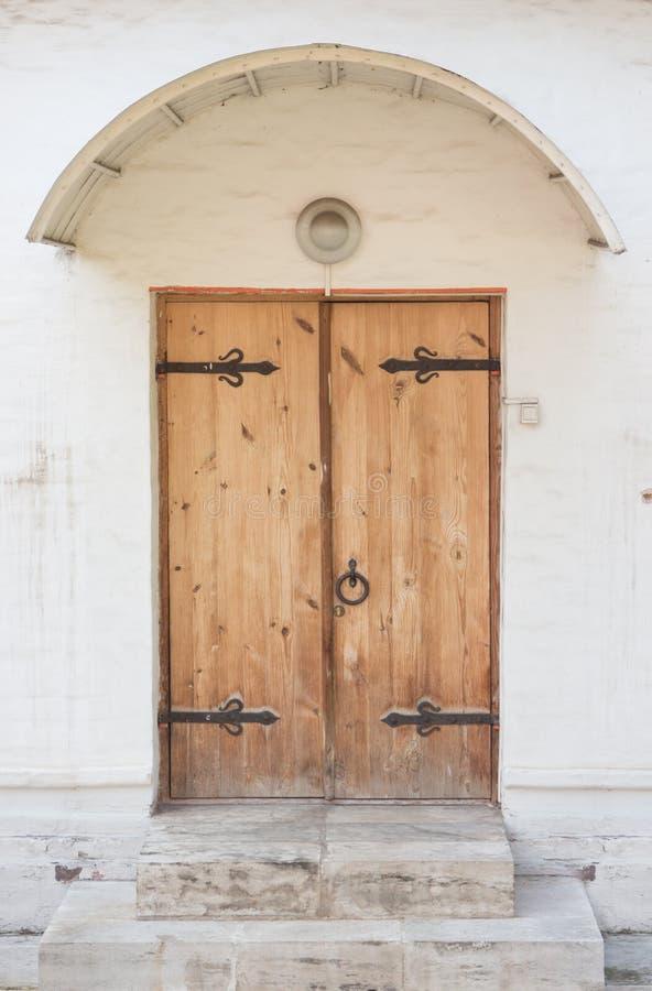 Historische aufwändige Holztür in einem Steineintritt stockfotos