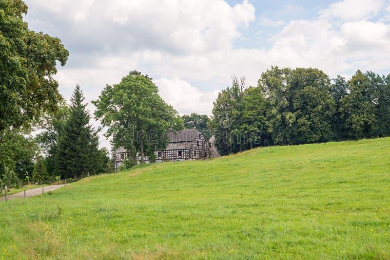 Historische gezimmerte Scheune des alten Gutshauses mit grüner Wiesenweide lizenzfreies stockfoto