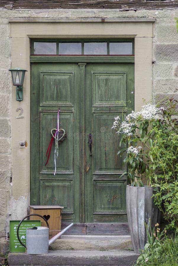 Historische Holztür, 2 belaubt, mit Steintreppenhaus, Blumendekoration und Schmiedeeiseninstallation lizenzfreies stockfoto
