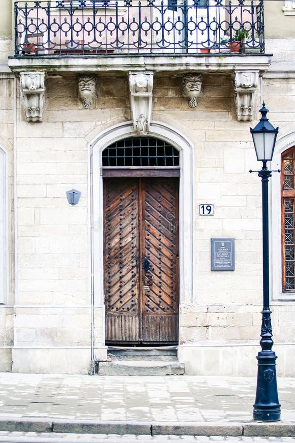 Historische Holztür mit kratzendem Balkon an der Laterne stockbild