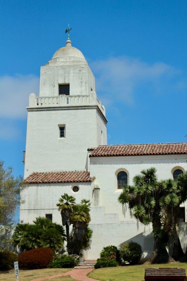 Historische Opdrachtkerk, San Diego, Californië met blauwe hemelachtergrond, bomen in voorgrond stock fotografie
