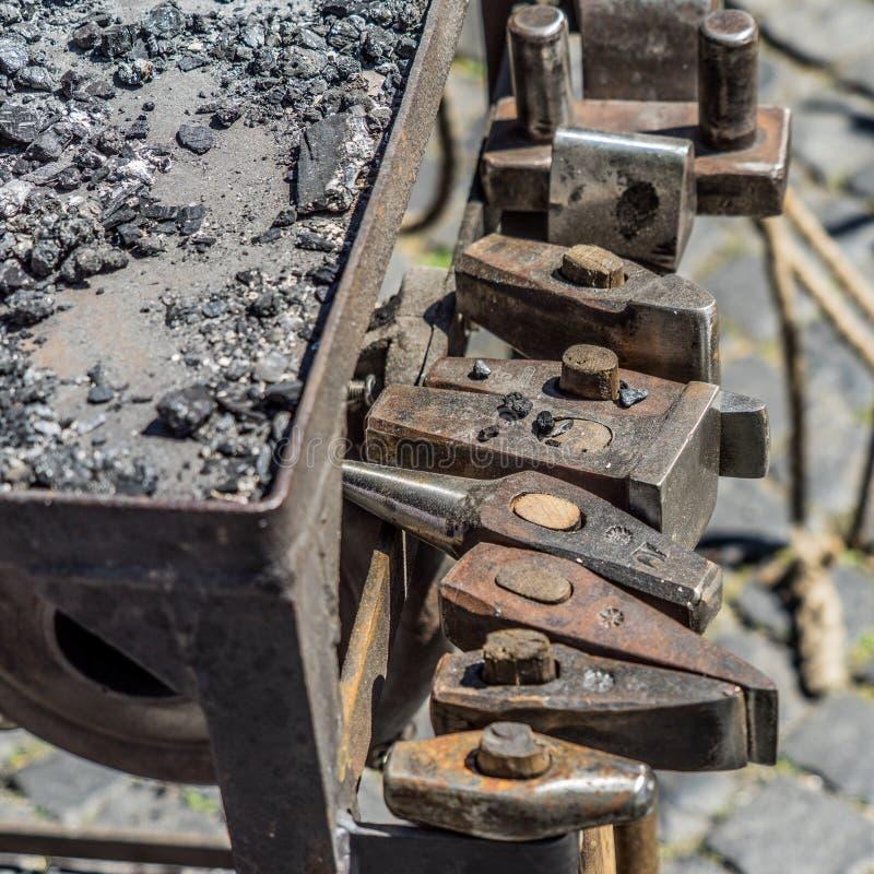 Historische Werkzeuge eines Schmiedes an einem mittelalterlichen Markt wie Hammer, Meißel, Ahle, Meißel, schlagende Platte, Stamp stockbild