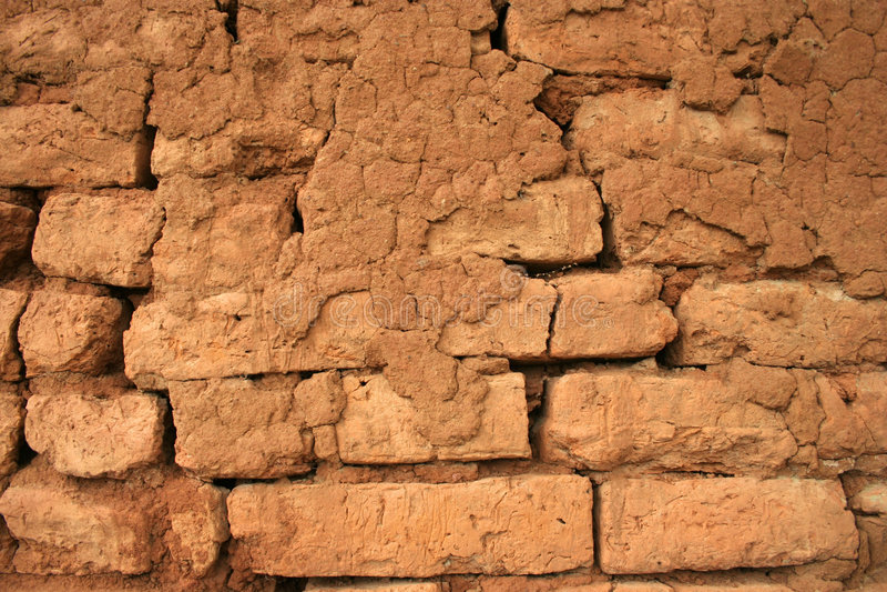 Historischer sonnengetrockneter Backsteinmauerhintergrund stockfotografie