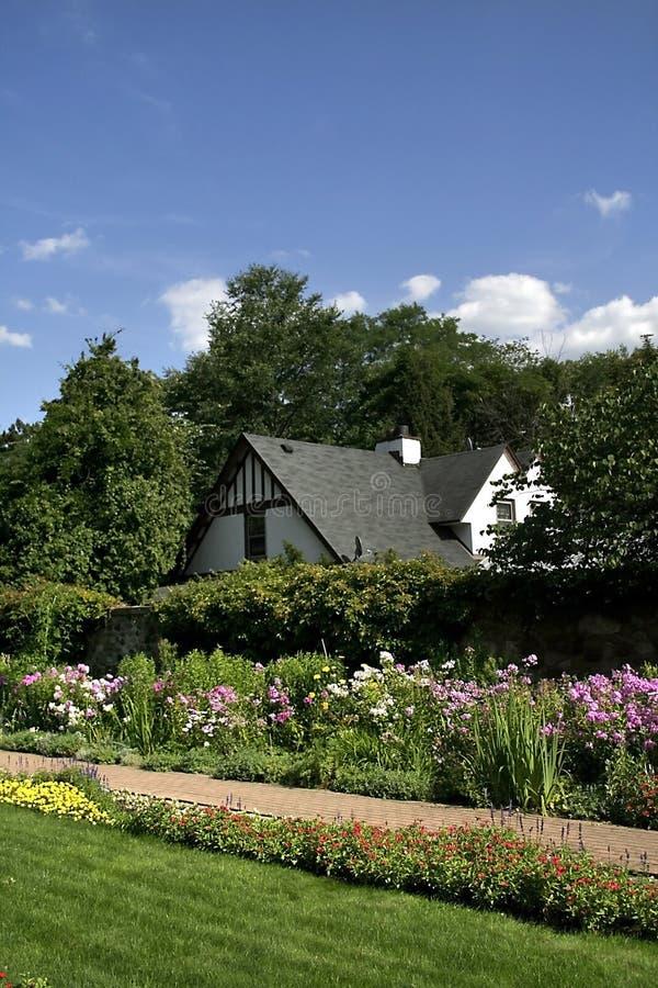 Historisches Haus und Blumen-Garten stockbild