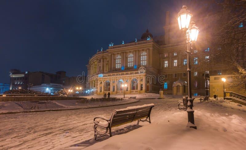 Historisches Odessa-Opern- und -balletthaus mit Lampe und Baum im Winter Schnee nachts lizenzfreies stockbild