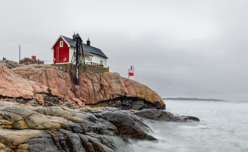 Historisk byggnad och liten fyr i området av Femöre, Sverige royaltyfri bild