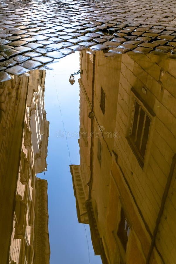 Historisk byggnadsreflexion i en pöl fotografering för bildbyråer
