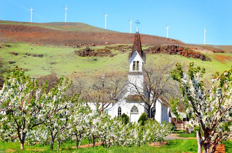 Historisk gammal kyrka i fruktträdgård fotografering för bildbyråer