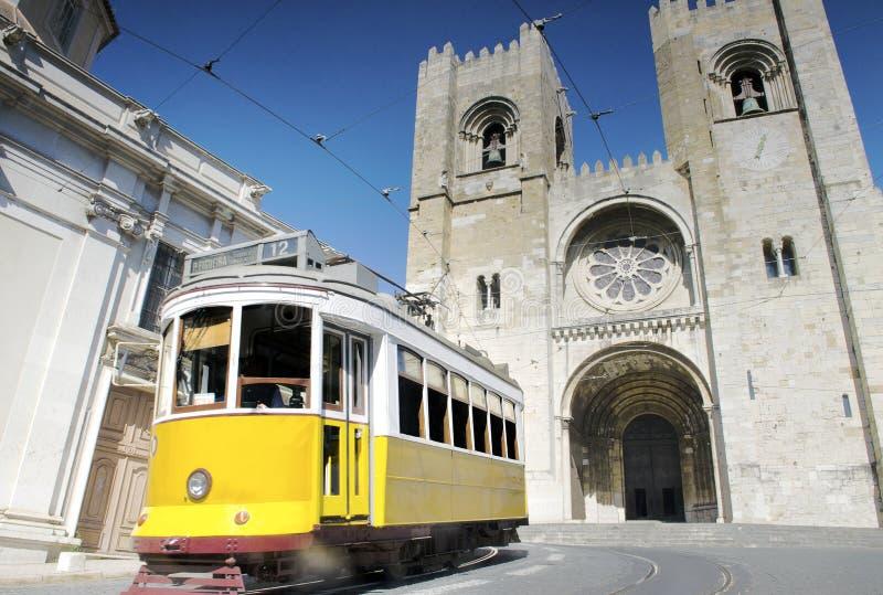 Historisk gul spårvagn framme av den Lissabon domkyrkan, Portugal royaltyfria foton