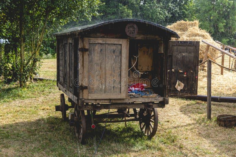 Historisk herdegodsvagn omvandlad till strömfördelare med samtidig regn och solsken och vattenånga över taket, i royaltyfria bilder