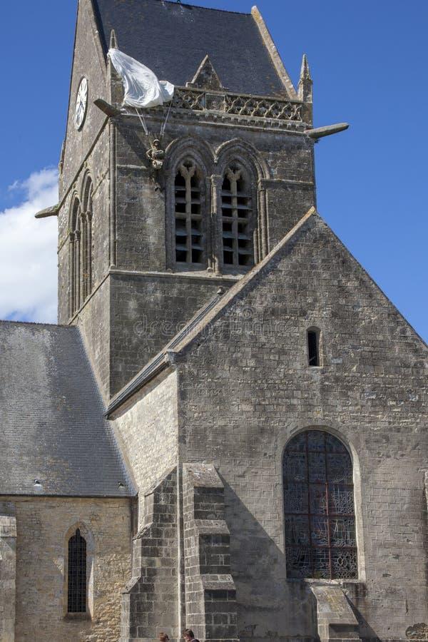 Historisk kyrka av Sainte bara l 'eglise, med en fallskärmsjägare som hänger på klockatornet fotografering för bildbyråer