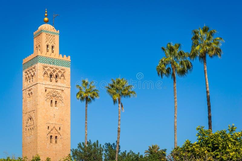 Historisk minaret och palmträd arkivfoto