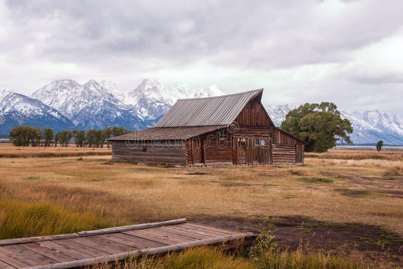 Historisk Moulton ladugård med snö-täckte berg i älgen, Wyoming royaltyfri fotografi