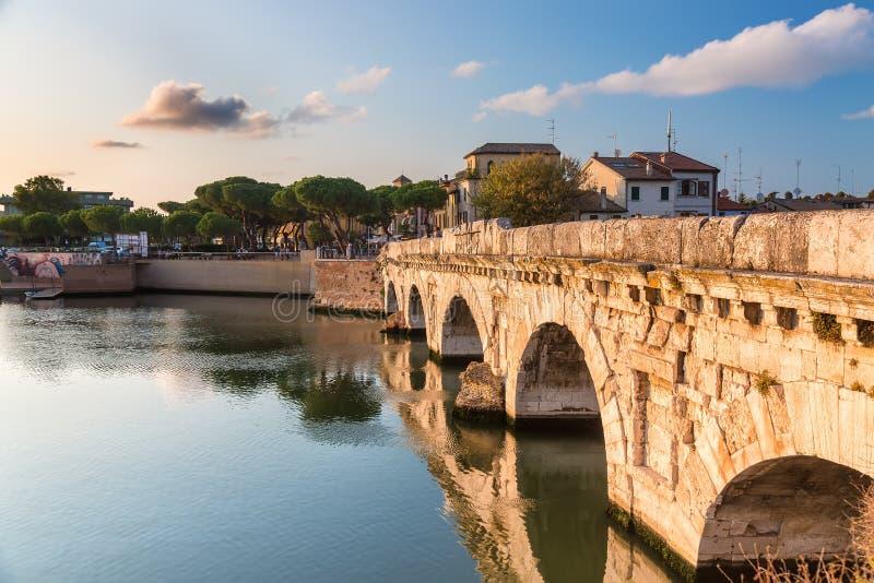 Historisk roman Tiberius bro över den Marecchia floden under solnedgång i Rimini, Italien arkivbilder