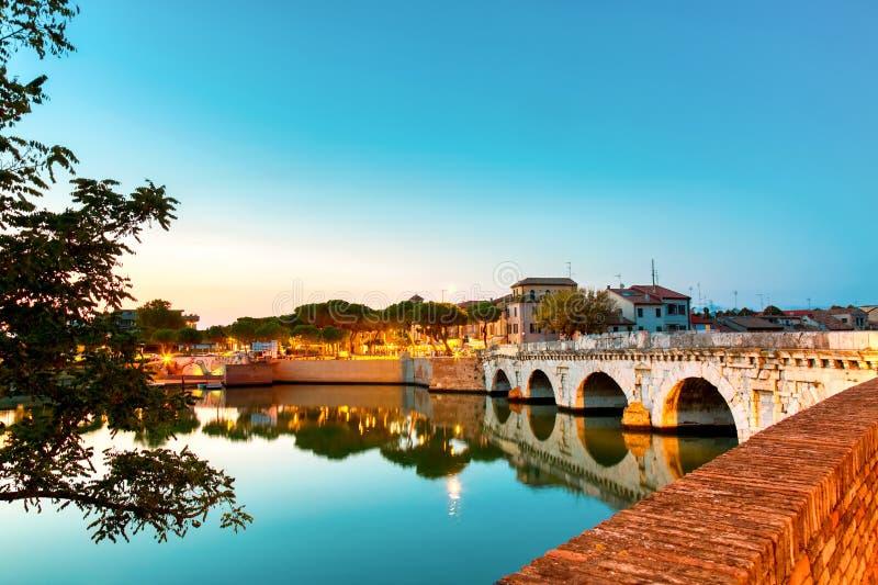 Historisk roman Tiberius bro ?ver den Marecchia floden under solnedg?ng i Rimini, Italien arkivbilder