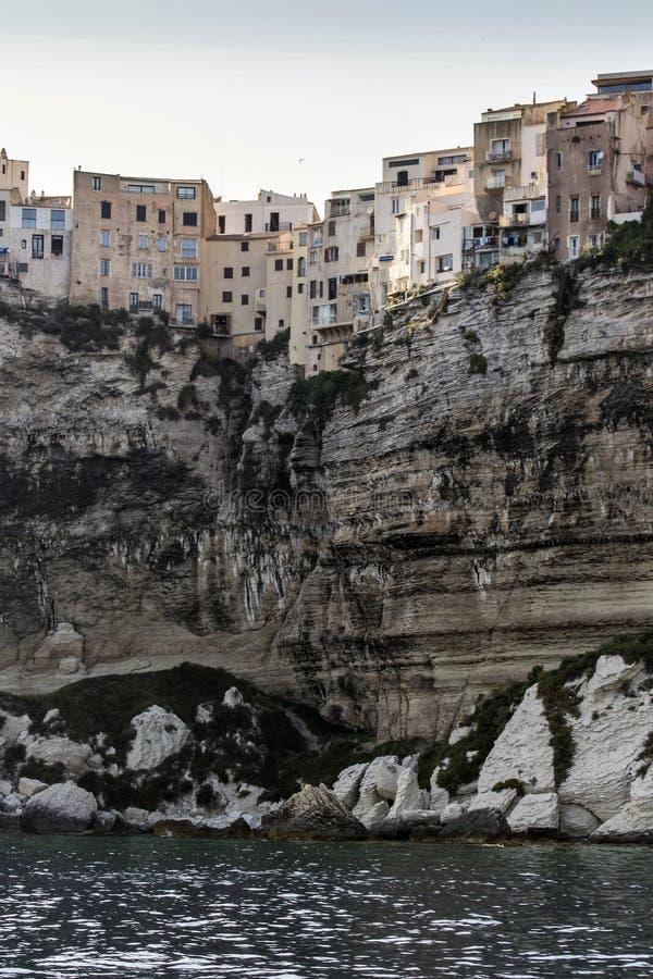Historisk stad med små hus på en vit klippa som förbiser havet i porten av Bonifacio royaltyfri foto