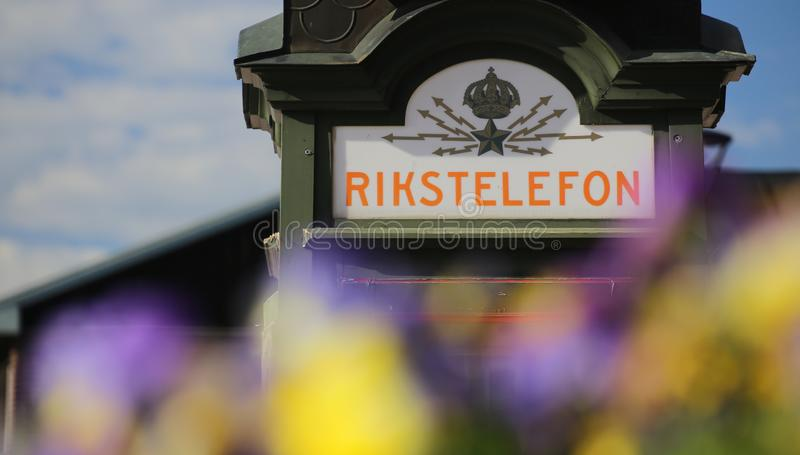 Historisk telefonask framme av den Bodens centralstationen (som byggs i 1893) i Lapland Rikstelefon betyder att kungariken ringer royaltyfri fotografi
