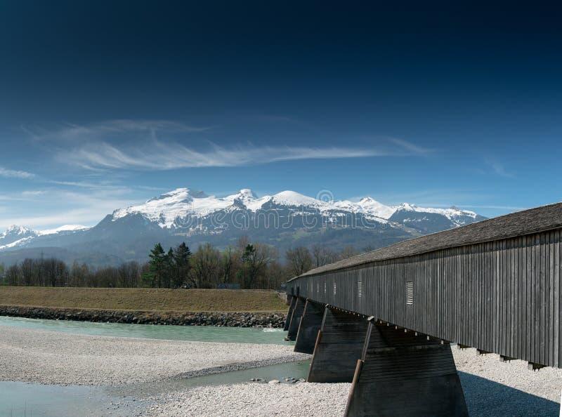 Historisk trädold bro över Rhen med berglandskap och blå himmel i bakgrunden royaltyfri fotografi