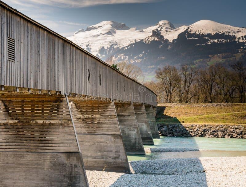 Historisk trädold bro över Rhen med berglandskap och blå himmel i bakgrunden royaltyfri foto