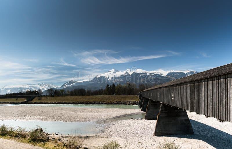 Historisk trädold bro över Rhen med berglandskap och blå himmel i bakgrunden fotografering för bildbyråer