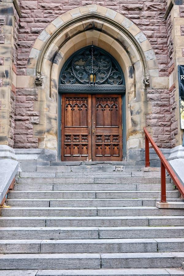 Historisk träingångsdörr av en gotisk kyrka och trappa fotografering för bildbyråer