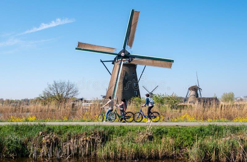 Historisk väderkvarn med cyklister i förgrund, på Kinderdijk, Holland, Nederländerna, en UNESCOvärldsarv royaltyfri foto