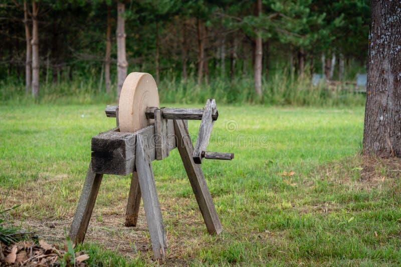 Historiska hjälpmedel Ett gammalt, hand-fungerings och att vässa hjälpmedlet - en slipsten arkivfoton