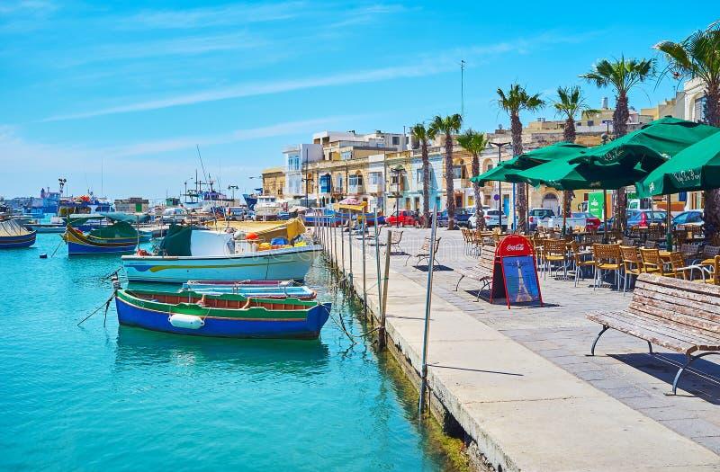 historiska stora byggnader och förtöjde maltesiska luzzufartyg, Marsaxlokk arkivfoto
