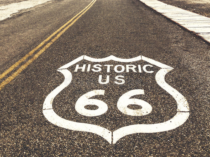 Historiskt huvudvägtecken för USA Route 66 på asfalt i Oatman, Arizona, Förenta staterna Bilden gjordes under en motorcykelvägtur royaltyfri bild