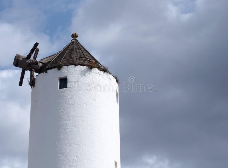 Historyczny stary biały wiatraczek w ciutadella menorca przeciw błękitnemu chmurnemu niebu fotografia royalty free