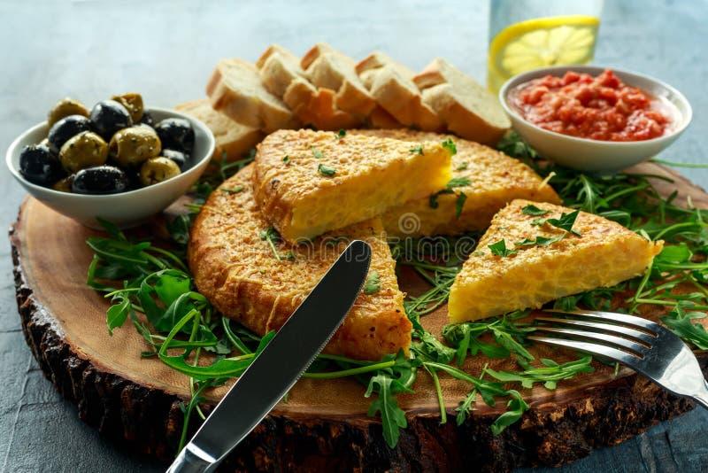 Hiszpański klasyczny tortilla z grulami, oliwkami, pomidorami, rucola, chlebem i ziele, zdjęcie royalty free