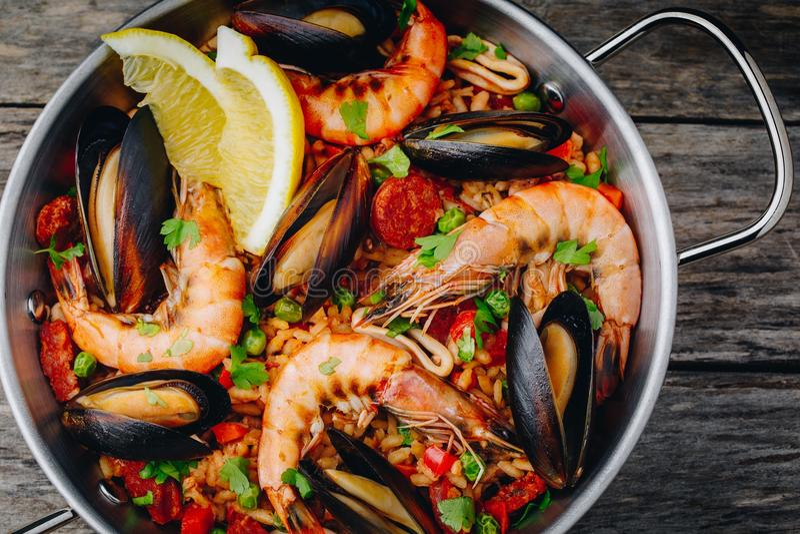 Hiszpański owoce morza paella z mussels, garnelami i chorizo kiełbasami w tradycyjnej niecce na drewnianym tle, obrazy stock