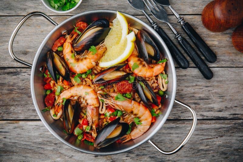 Hiszpański owoce morza paella z mussels, garnelami i chorizo kiełbasami w tradycyjnej niecce na drewnianym tle, zdjęcia royalty free