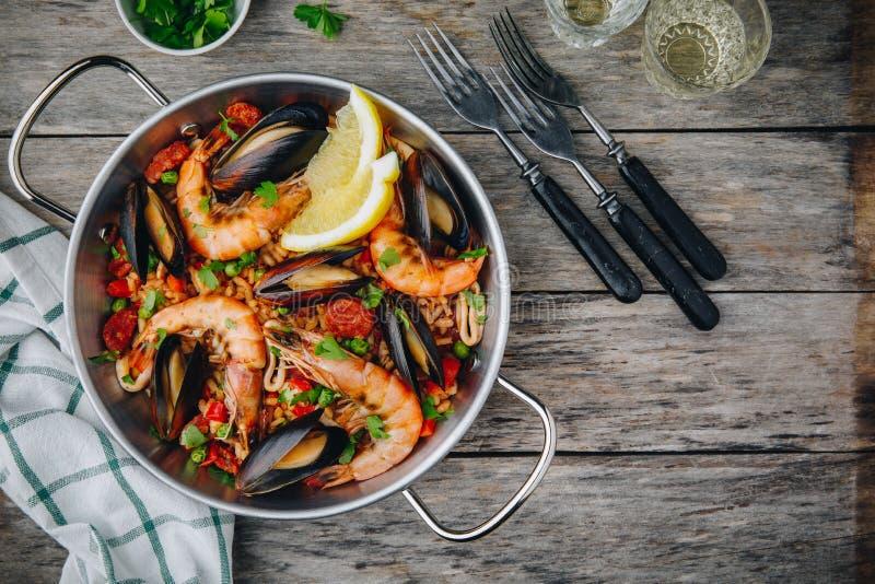 Hiszpański owoce morza paella z mussels, garnelami i chorizo kiełbasami w tradycyjnej niecce na drewnianym tle, obraz stock
