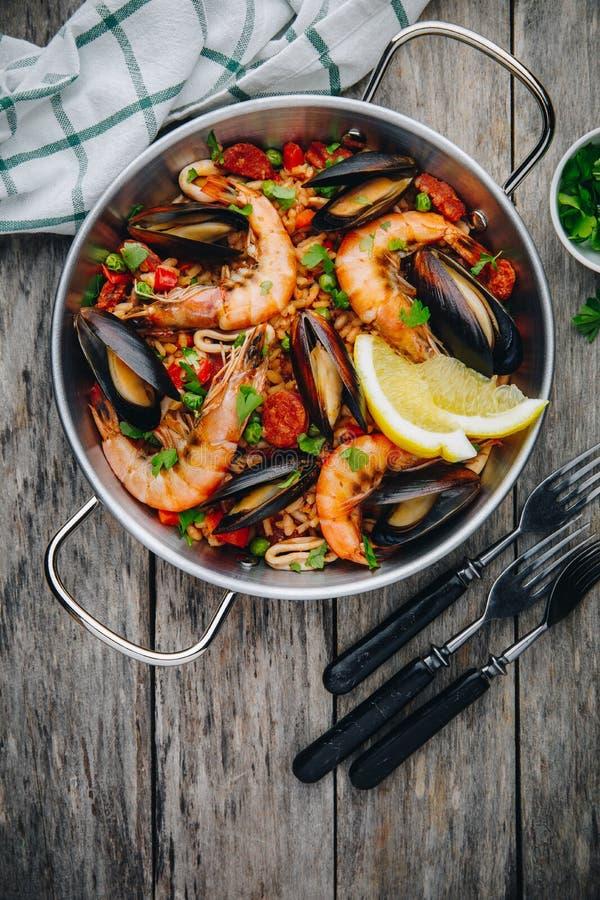 Hiszpański owoce morza paella z mussels, garnelami i chorizo kiełbasami w tradycyjnej niecce na drewnianym tle, zdjęcie royalty free