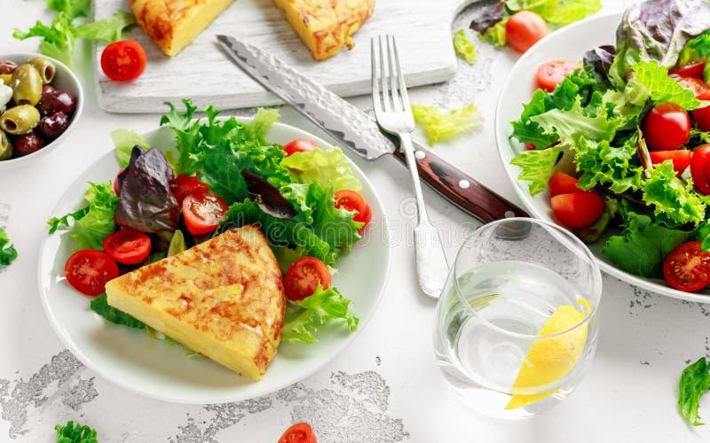 Hiszpański tortilla, omelette z grulą, cebula, warzywa, pomidory, oliwki i ziele w białym talerzu, śniadanie fotografia stock