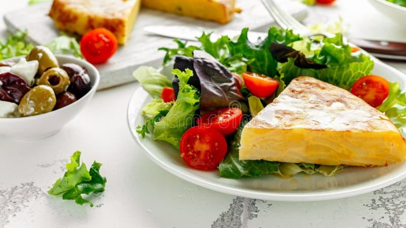 Hiszpański tortilla, omelette z grulą, cebula, warzywa, pomidory, oliwki i ziele w białym talerzu, śniadanie zdjęcie stock